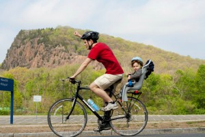 A young man rides a bike carrying a young child in a seat. He pumps his fist and cheers during the Rock to Rock Earth Day ride.