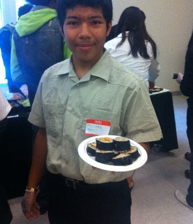 Sophomore Marcel holds up his handmade sushi role at Tuesday's Youth Summit