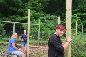 Melissa Spear instructs summer site crew as they measure for the blueberry enclosure.