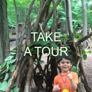 "A young boy gives thumbs up as he stands in front of a fort he helped construct with branches in leaves in the woods. The words ""Take a tour"" are written across the image."