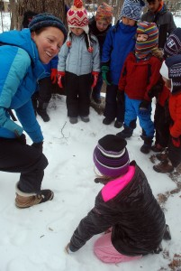 A group of young children and a teacher explore the woods and discover animal tracks in the snow.