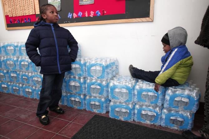 Justin Roberson (left), age 6, and Mychal Adams, age 1, wait on a stack of bottled water at a rally where the Rev. Jesse Jackson was speaking about about the water crisis in Flint, Michigan, Jan. 17, 2016. PHOTO: BILL PUGLIANO/GETTY IMAGES