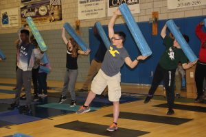 Rows of students stand on yoga mats and hold foam rollers over their heads during a class in flexibility at the JCC.