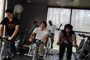 Students and a teacher exercise bikes during a spin class at the JCC.