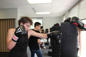 A high school student wearing boxing gloves works out during a strike class by hitting a punching bag.