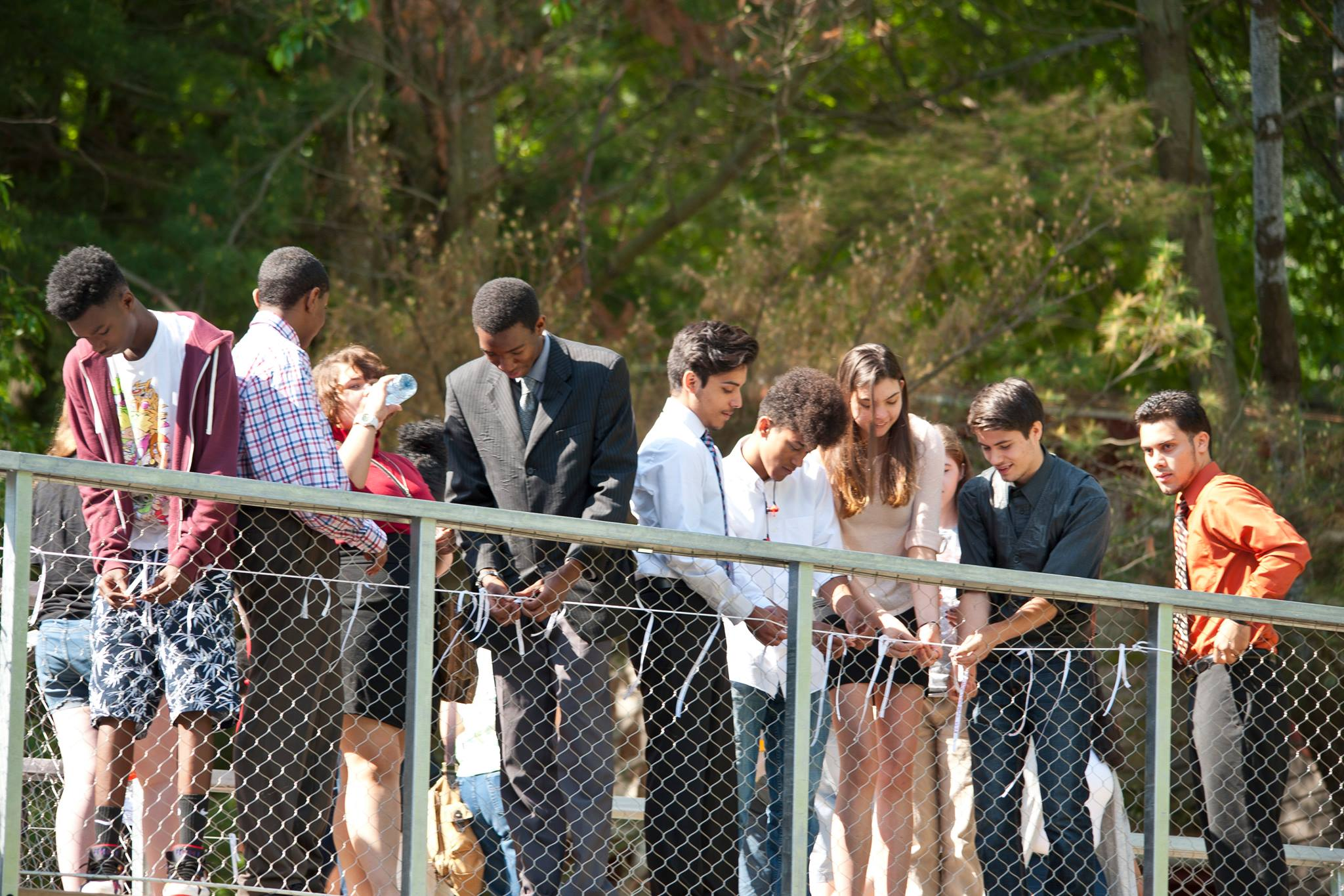 Students tie wishes written on ribbons to the bridge of the new Common Ground High School building.